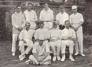 A cricket team arranged in two rows. Most are wearing cricket whites and caps.