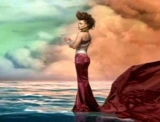 "Call on Me (Janet Jackson song) - Jackson wearing a maroon-colored gown standing in an ocean while clouds can be shown in the background in the ""Call on Me"" music video. It is noted as one of the most expensive music videos ever made"