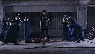 Netsuai Hakkakuchū - Sheena as Linnko about to attack paparazzi (played by Idevian Crew) in the music video.