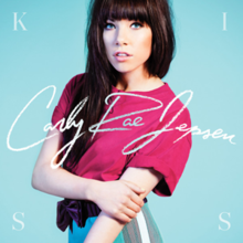 "The album cover shows Carly Rae Jepsen against a light blue background. She is photographed from the waist up, holding her left arm with the opposite hand, and is wearing a pink T-shirt. Across the middle of the cover, ""Carly Rae Jepsen"" is written in white cursive text. The letters of the word ""kiss"" appear in each corner clockwise in white, all-capital text."