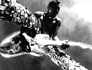 "Give It Away (Red Hot Chili Peppers song) - Frusciante playing a reflective silver Fender Stratocaster and wearing sequined pants in the music video for ""Give It Away""."