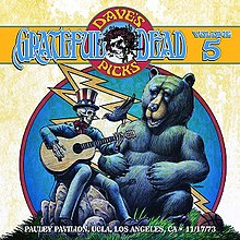 A skeleton dressed as Uncle Sam plays a guitar. A bear seated nearby, and a crow sitting on the bear's shoulder, listen. A basketball lies in the grass.