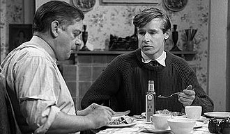Ken Barlow - Frank (left) and Ken (right), in the Barlows' first scene. The juxtaposition of Frank eating in his shirtsleeves, meal smothered in brown sauce, and Ken in a tie, disdainful of the condiment, was used to establish Ken's characterisation as a snob, in conflict with his parents over his rejection of his working-class roots.