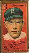 "An old-fashioned baseball card of the kind packaged with cigarettes. On a red background is a drawing of a young man's hand and shoulders; he has a serious look on his face and is wearing a blue baseball cap marked ""B"", for ""Brooklyn"". Above his head the letter ""B"" is repeated, and the team's nickname, ""Superbas"" is given. Below an autograph – ""Geo N Rucker"" – is reproduced, along with a caption; ""of the Brooklyn Nationals""."