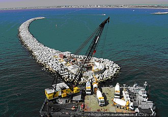 Accropode - Large accropode units are lowered into a position offshore by aid of a crane.