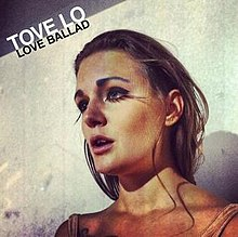 "Artwork for ""Love Ballad"". A woman with brown hair and wearing fake eyelashes is looking forward. Above her image, the words ""Tove Lo"" are written with white letters, as well as the words ""Love Ballad"", which are written with black letters."
