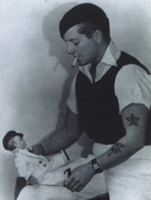 Three-quarter length portrait of a tattooed, short-haired woman in casual, male clothing. She is smoking and looking down at a doll she is holding.