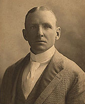 Portrait of a man in a jacket with a dark collar wearing a white shirt and tie.
