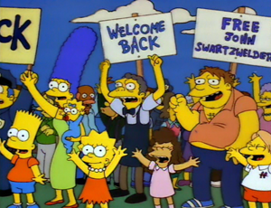 "Hurricane Neddy - A scene from the episode, featuring a sign reading ""Free John Swartzwelder"", referencing one of the series' writers"