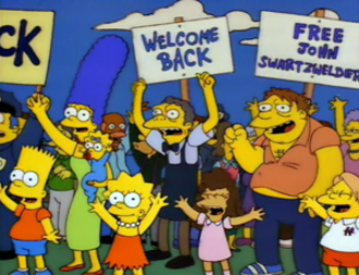 """Hurricane Neddy - A scene from the episode, featuring a sign reading """"Free John Swartzwelder"""", referencing one of the series' writers"""