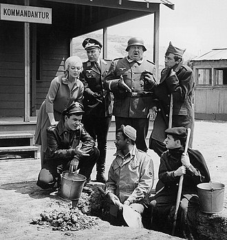 Hogan's Heroes - The cast of the show. From left to right: Fräu Helga, Colonel Hogan, Commandant Klink, Seargent Schultz, Sergeant Kinchloe, Corporal LeBeau, and Corporal Newkirk. Sergeant Carter is absent from the image