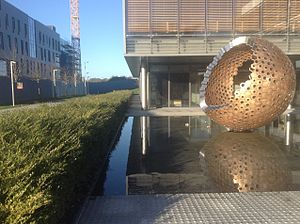 "Maynooth University - Sculpture ""Dance"" in front of the Íontas Building, with the Eolas Building in the background"
