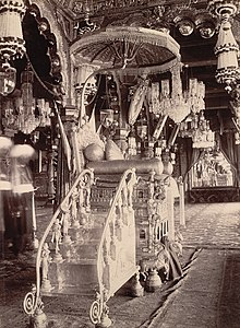 A black and white picture of an ornamented throne, constructed out of some metal. There are intricate carvings of horses on its base and of women on the steps leading up to it. An umbrella rises above the throne and many chandeliers surround it.