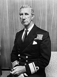 Portrait of a man in naval uniform. Visible from the waist up, he appears to be sitting and wears a dark, formal naval jacket that sports the rank of rear admiral. There are medal ribbons on his left breast, and he is holding a smoking pipe in his left hand.