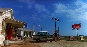 "A flat, rural setting under a vast sky. On the left, a man sits on the porch of a small, old wooden building. In front of him, another man stands beside a pickup truck parked next to a gas station pump. On the right, a tall red sign reads ""Mariposa Motel""."