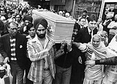 Peach's coffin being carried by Sikhs, as part of a multiracial procession