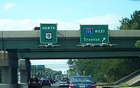 A four lane divided highway passing under a freeway. A set of Township green signs are attached to the freeway overpass, with the sign on the left reading north U.S. Route 9 and the sign on the right reading Interstate 195 west Trenton with an arrow pointing to the upper right.