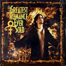 Prince stands with his arms out while wearing a brown robe in front of a golden portrait displaying the title of the song