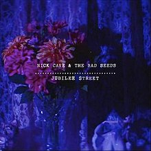 "An image of purple flowers against various shades of blue. White text reads ""Nick Cave & the Bad Seeds Jubilee Street"""