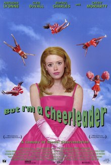 "A half-length portrait of a young woman with long hair, wearing a bright pink formal dress and satin gloves. Behind her at a distance five cheerleaders in orange cheer-leading outfits perform cheer-leading maneuvers whilst falling through a bright blue sky. Across the portrait reads, in green, ""But I'm a Cheerleader"", and below, in smaller letters, ""A Comedy of Sexual Disorientation"". At the top of the picture, in small letters are the names ""Natasha Lyonne, Clea Duvall, RuPaul Charles and Cathy Moriarty""."