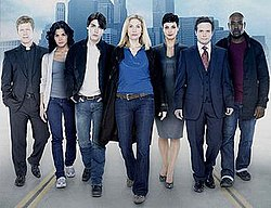 Seven cast members of V in a line with a city backdrop.