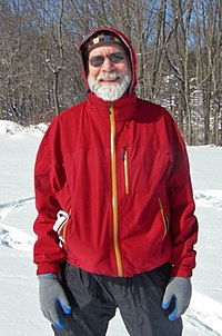 A man with a white beard, mustache and sunglasses, wearing a hooded red jacket with yellow zipper, and blue jeans, photographed in winter with snow and bare trees behind him