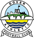 "A simplified illustration of a castle atop white cliffs, with the sea below, all surrounded in a circular border containing the words ""Dover Athletic"", with a scroll below containing the words ""Football Club"""