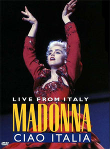 Madonna in short cropped hair, wearing a red flamenco dress. She puts up both of her hands above her head