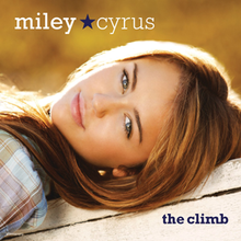 "A female teenager lies on her back with her head is tilted over. The teen wears a plaid shirt, pink lipstick, and has blue green eyes. The words ""Miley"" and Cyrus"", separated by a blue star, are printed in white above her face, and the words ""the climb"" are printed below her face."