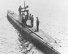 Un submarino flota en la superficie con su tripulación de pie en la cubierta y en la torre de mando.  La insignia naval de Austria-Hungría se puede ver volando desde la torre de mando del submarino y la escotilla de entrada principal del barco está abierta.