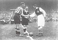 Two football players shake hands in front of a referee over the pitch's center circle.