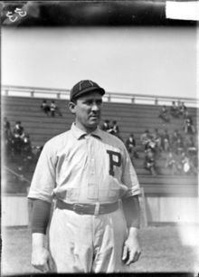 "A black-and-white photograph of a man in a white old-style baseball uniform with a dark-colored ""P"" over the left breast"
