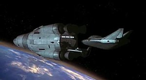 A pair of spacecraft, both designed to a curved aesthetic, orbit an Earth-like planet. One vessel, smaller than the other, is a shuttle departing from the docking port of the mothership.
