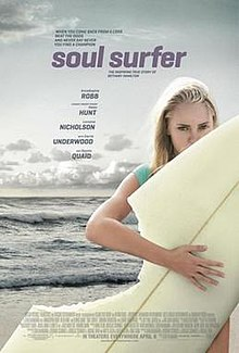 A young girl holds a surfboard at the beach. A section of her board is missing as if been bitten by a shark