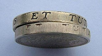 Coin counterfeiting - A real British pound coin, of the old type, on top of a fake. This coin was often counterfeited.