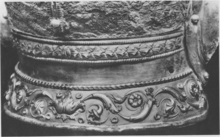 Black and white photograph of the neck guard of the Emesa helmet, showing the three layers of decoration: a torus of ivy leaves bordered by cords at the top, a smooth silver section in the middle, and an acanthus scroll decoration at the bottom.