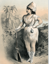 moderately buxom white woman standing, holding a rifle and wearing a costume intended to suggest a castaway