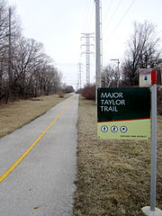 "View down a bike trail, with a sign saying ""Major Taylor Trail"" on the right in the foreground"