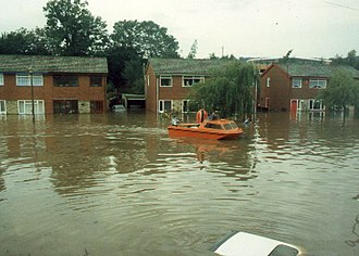Appley Bridge - Syd Hill comes to the rescue with a small personally owned motor launch - the top of a car is visible on the drive, giving a clear indication of water depth