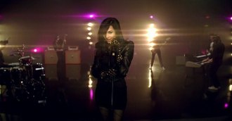 """Remember December - Lovato performing on stage in the music video for """"Remember December""""."""