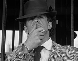 Black-and-white image of a man seen from mid-chest up, wearing a fedora and a jacket with a houndstooth-like pattern. He holds a cigarette between the middle and index fingers of his left hand and strokes his upper lip with his thumb, he stands in front of what appears to be a mirrored doorway.