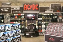 Inside a supermarket, boxes of the video game Rock Band, a display with music CDs, and a display with the AC/DC logo atop it, featuring shirts, CDs and the Rock Band instruments.