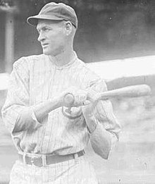 A black-and-white photograph of a man wearing a white pinstriped baseball uniform and holding a baseball bat over his shoulder with both hands