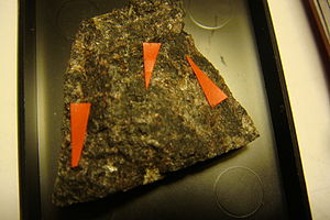 Epidote - Sample of dollaseite (dark brown matrix at arrow points) from Sweden