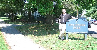 Gnadinger Park - Errin Gnadinger, grandnephew of Frank and Norb Gnadinger, and grandson of Carl Gnadinger next to the Gnadinger Park sign at the intersection of Reutlinger and Ellison Avenues in Louisville, Kentucky.