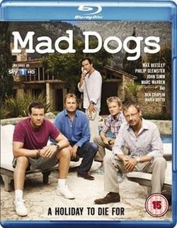 "A BD cover with the title ""Mad Dogs"" at the top. Underneath are five middle aged males, four are sitting while the fifth in the middle is standing and on the telephone. Behind them is a villa."