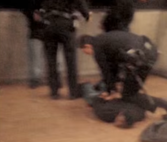 Shooting of Oscar Grant - A screenshot of Grant pinned down as police try to handcuff him, right after the shooting; this was captured from one of the videos that recorded the police incident