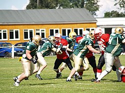 Players from two American football teams during a match. One team is wearing green shirts and gold pants, the other team is wearing red shirts with black pants