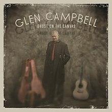 """La diskkovraĵotrajtoj Campbell portanta longan nigran mantelon starantan kun malferma gitaro-kazo al lia rajto kaj akustika gitaro al lia rajto. Super li estas la vortoj """"GLEN CAMPBELL=/=GHOST ON THE CANVAS"""" verkita en blanka."""