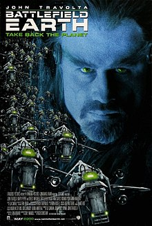 Movie poster which reads: John Travolta / Battlefield Earth / Take Back The Planet. A man's face with a goatee beard appears in the background, and alien spaceships in the foreground.